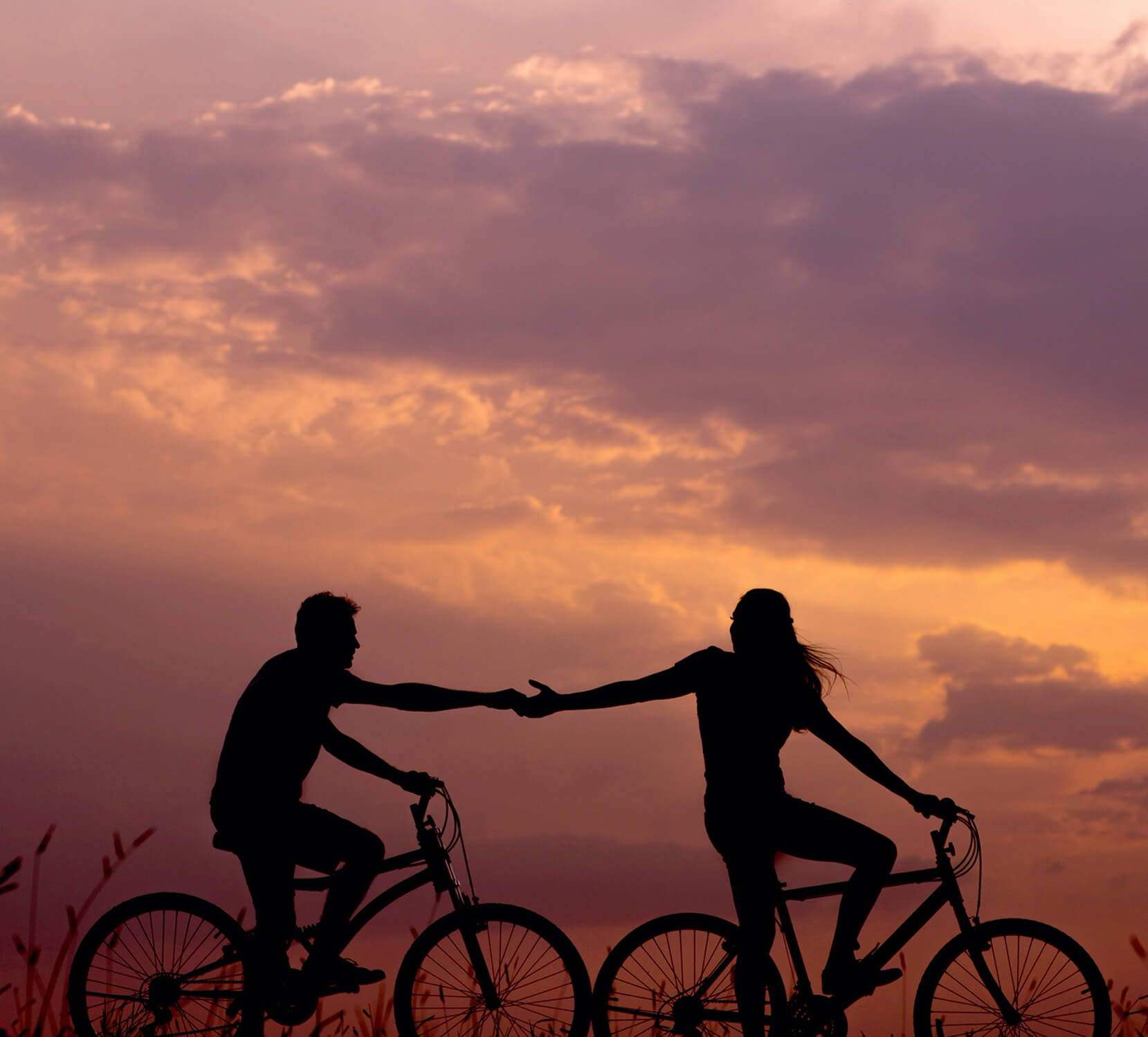 woman on bike reaching for man's hand behind her also on bike photo
